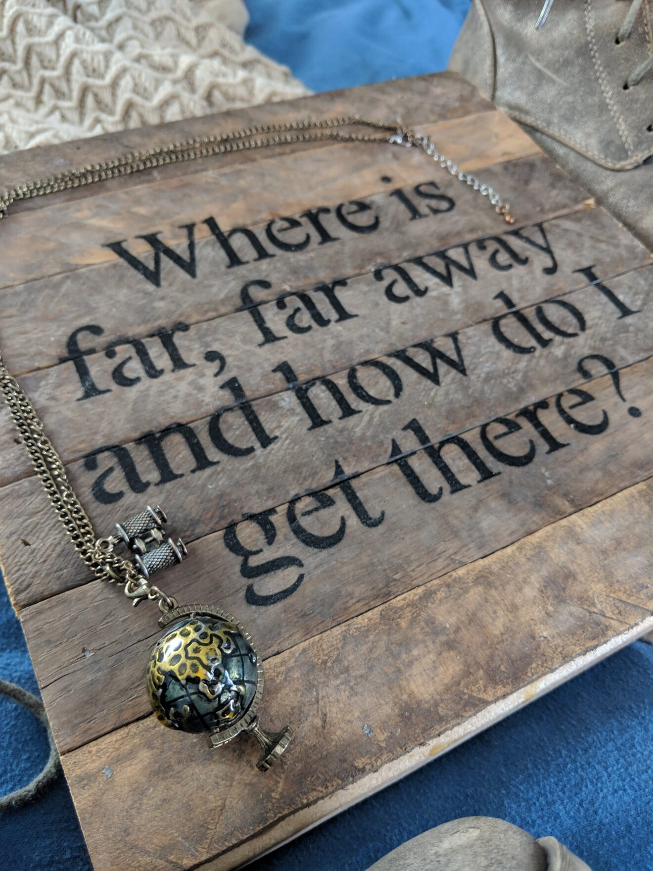 Story Behind the Cloth Where is far far away and how do i get there quote on wood canvas adventurous shoes earth globe necklace flatlay photography 5 angled closeup